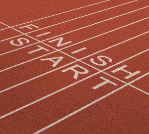 Image of a portion of a reddish brown running track with painted lane divisions crossed by a perpendicular line with