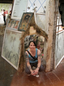 Author Kam Oi Lee crouching in front of a display of many large paintings